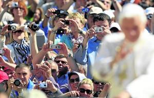 Los fieles hacen fotos del papa Benedicto poco antes de que dimitiese