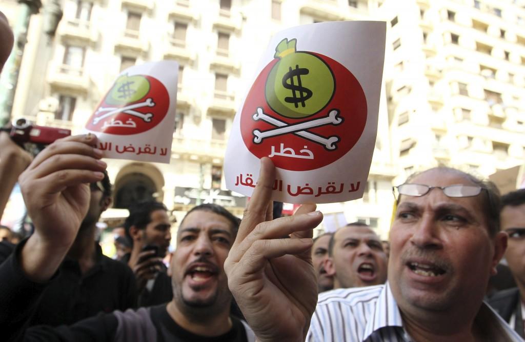 """Un grupo de egipcios muestran unos carteles en los que se lee """"Dólares = peligro"""" en árabe"""
