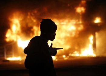 A man walks past a burning building during rioting after a grand jury returned no indictment in the shooting of Michael Brown in Ferguson, Missouri November 24, 2014. Gunshots were heard and bottles were thrown as anger rippled through a crowd outside the Ferguson Police Department in suburban St. Louis after authorities on Monday announced that a grand jury voted not to indict a white officer in the August shooting death of an unarmed black teen.   REUTERS/Jim Young (UNITED STATES  - Tags: CRIME LAW CIVIL UNREST)   - RTR4FG7O