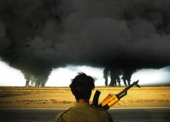 27 Sep 1990, Abadan, Jazire-ye Abadan, Iran --- An Iranian soldier watches as smoke billows from multiple burning oil refineries in Abadan, Iran. Abadan, which contains a high concentration of oil fields and refineries, became a front-line city during the Iran-Iraq War, resulting in most of the city being destroyed by Iraqi attacks. --- Image by © Henri Bureau/Sygma/Corbis